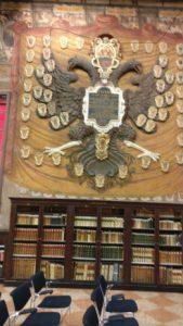 Escudo de una familia en clase de leyes, en la pared encima de una estantería