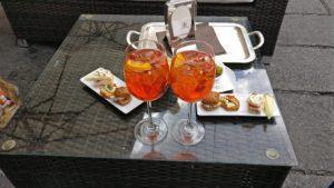 Aperitivo que incluye dos copas de aperol spritz (de color naranja), olivas muy grandes y bandejitas con diferentes montaditos